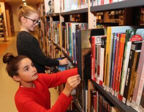 Collégiennes cherchant des livres sur un bibliothèque
