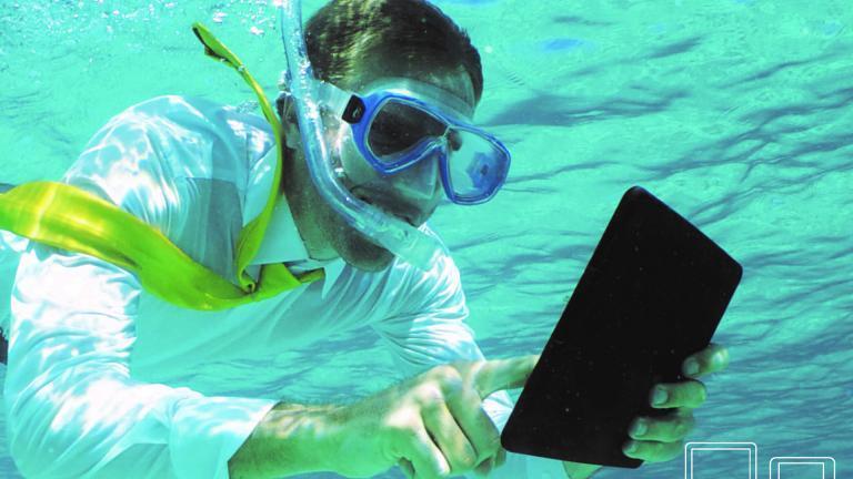 Homme sous l'eau avec masque et tuba consultant une tablette
